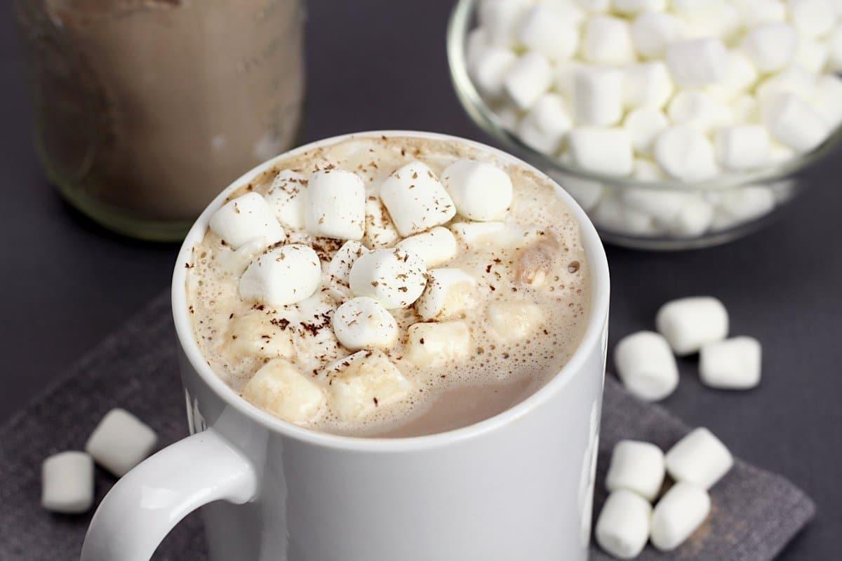 Mini marshmallows and chocolate shavings on top of a mug of hot chocolate.