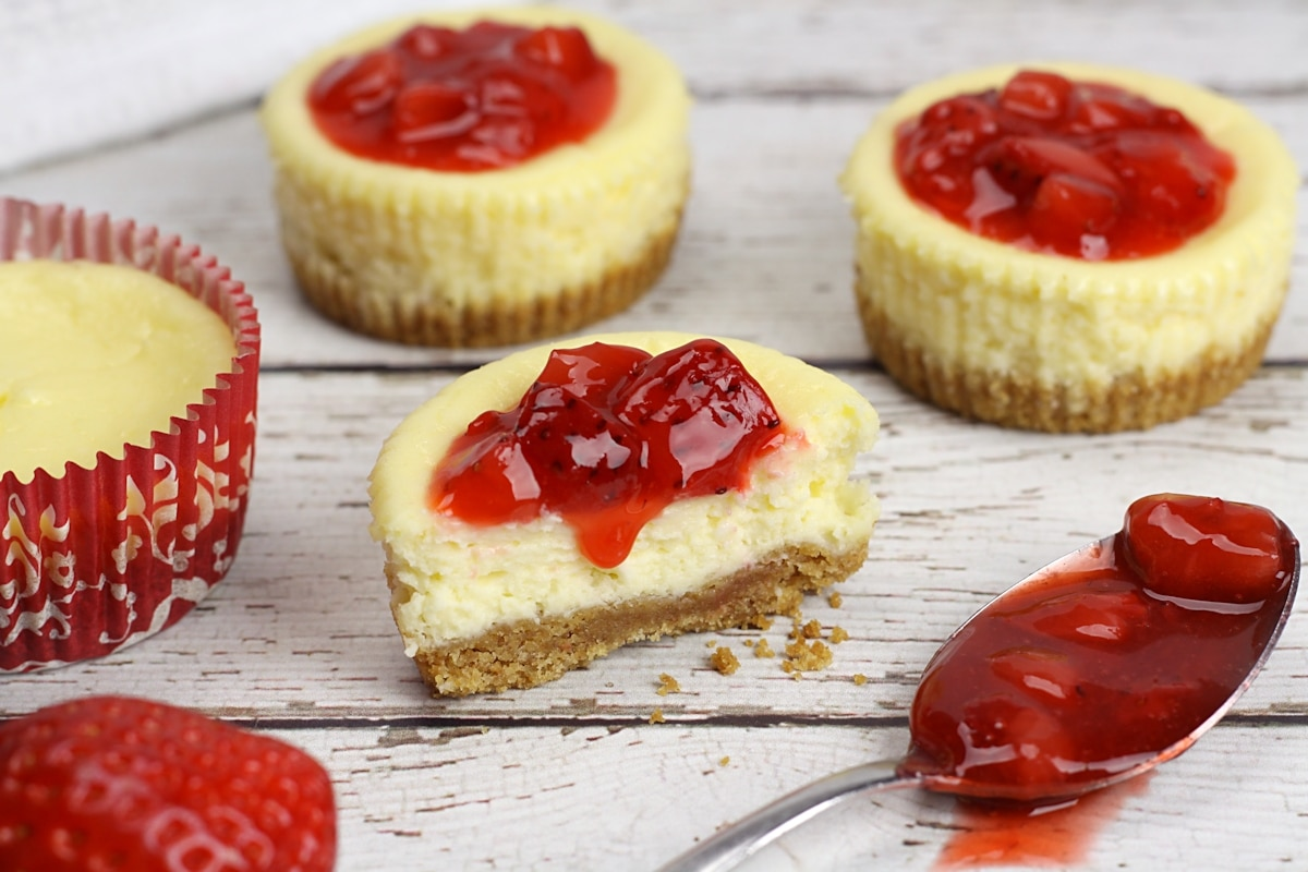 A cheesecake sliced in half with strawberry topping dripping down.