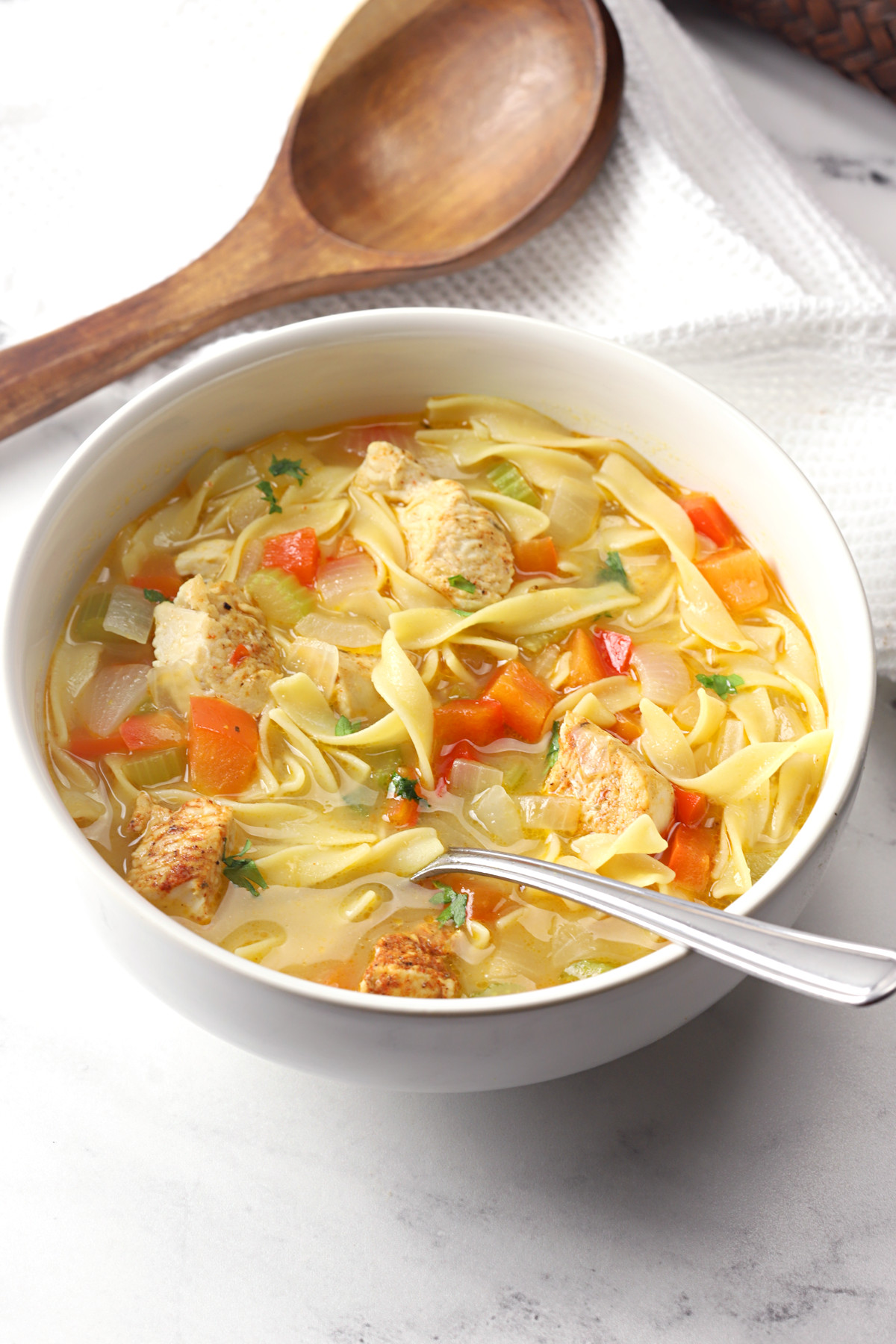 A white bowl filled with cajun chicken noodle soup.