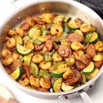 A saute pan filled with shrimp, sausage, and veggies.