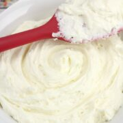 A white bowl of frosting with a red spatula.