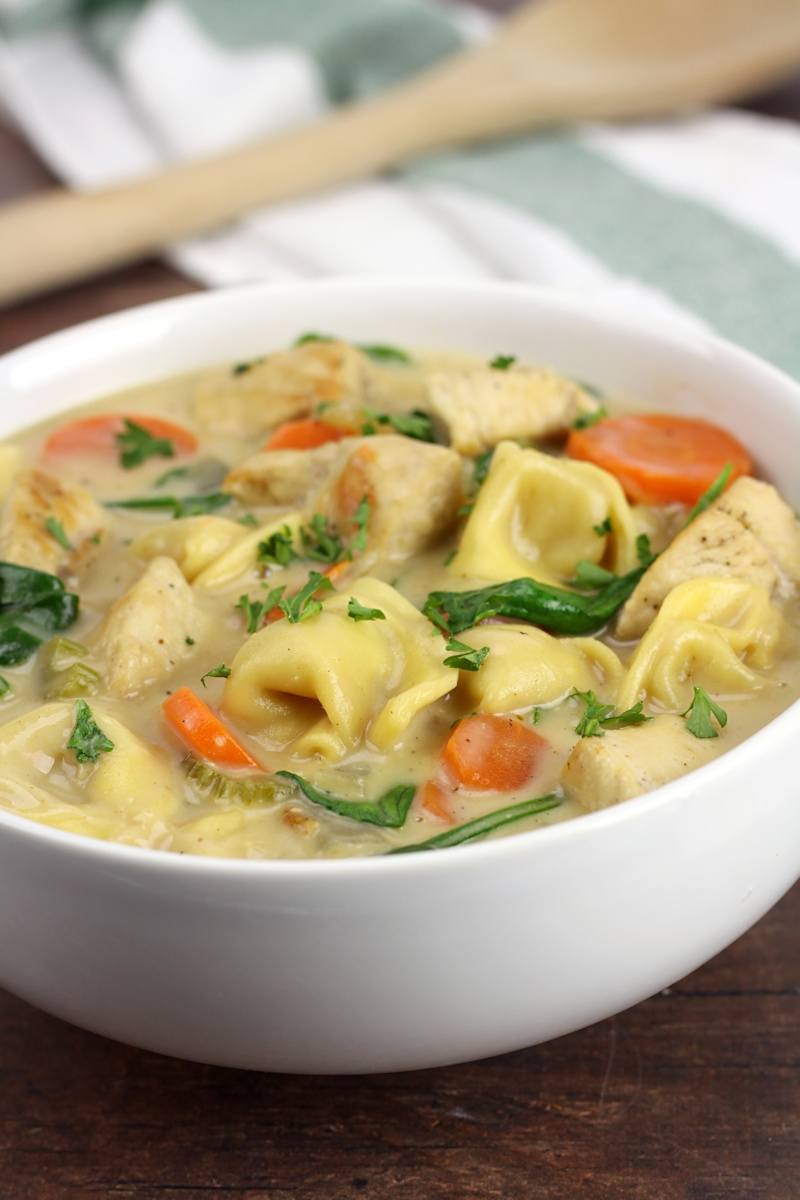A white bowl filled with tortellini soup.