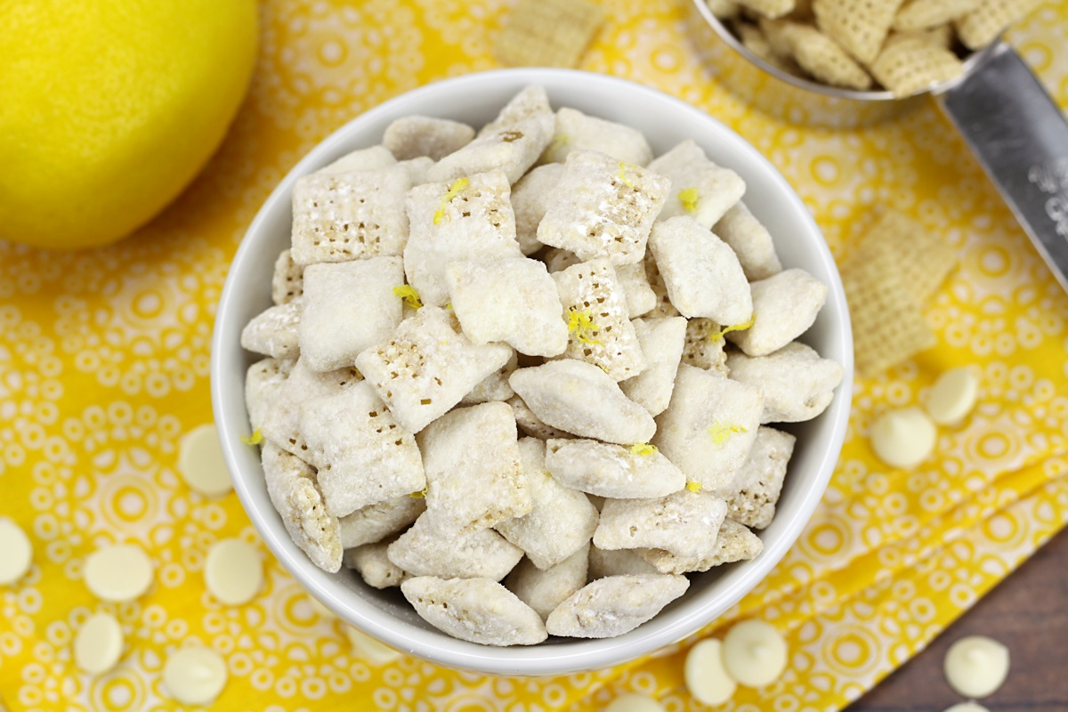 White bowl filled with puppy chow on a yellow napkin.