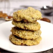 A stack of four cookies on a white plate.