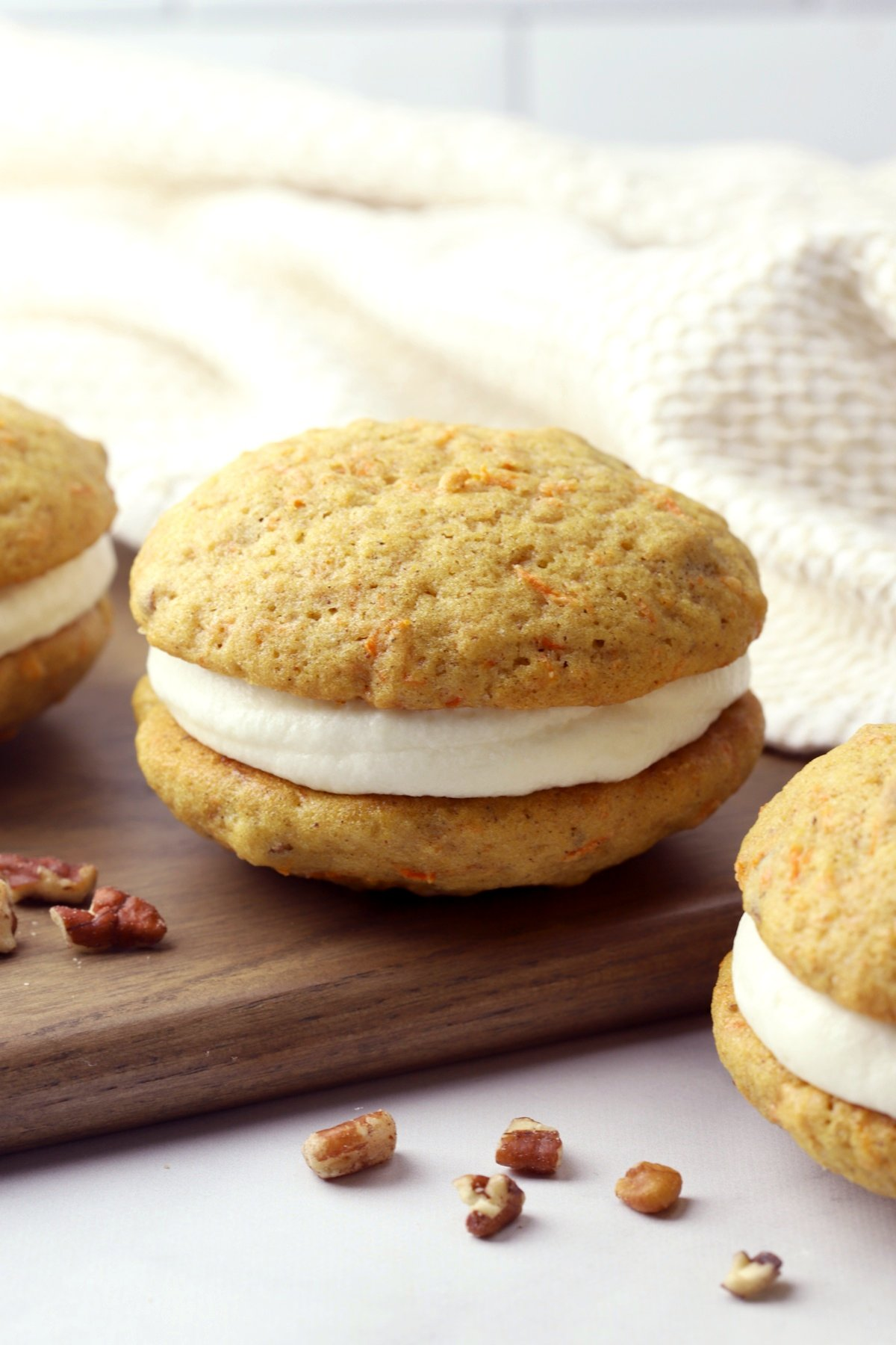 Carrot cake whoopie pies on a wooden cutting board.