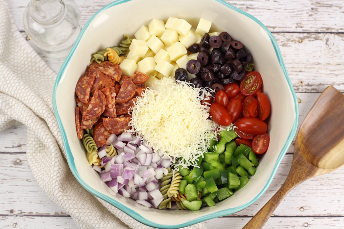 Ingredients for a classic pasta salad in a teal bowl, before being mixed together - mozzarella cheese, olives, cherry tomatoes, green bell pepper, red onion, pepperoni, and parmesan cheese.