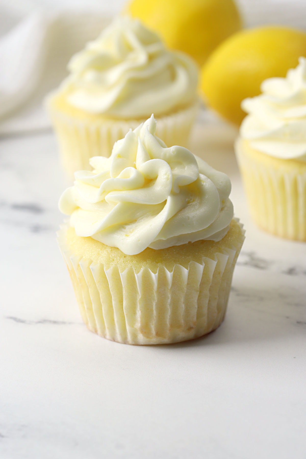 Lemon cupcakes on a marble counter top.