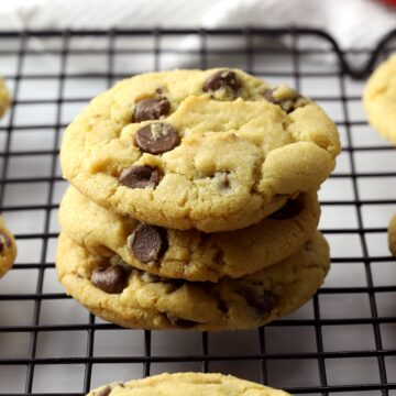 A stack of three chocolate chip cookies on a cooling rack.
