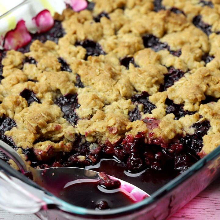 A metal spoon scoops out a serving of blueberry crisp.