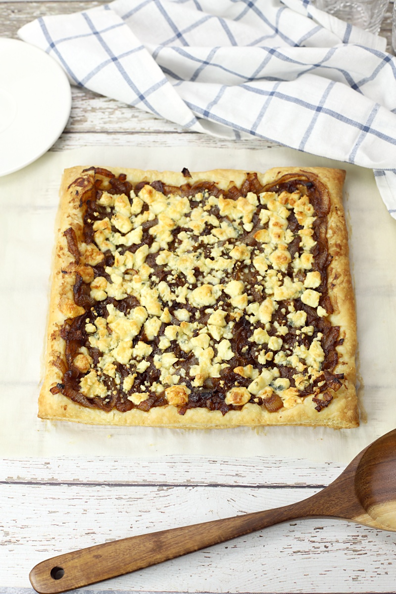 A whole tart laying on a white wood counter top.