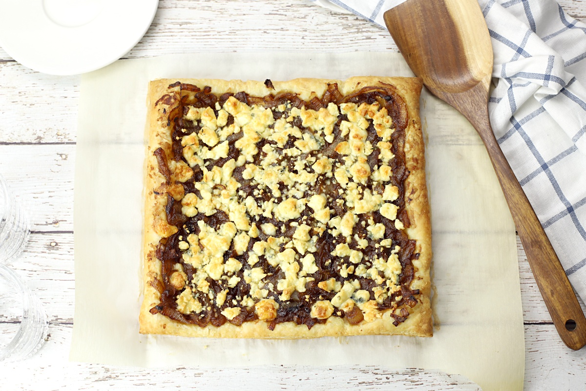 A whole caramelized onion tart, ready to be sliced and served.