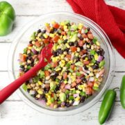 A bowl of cowboy caviar in a glass bowl with a red spoon.