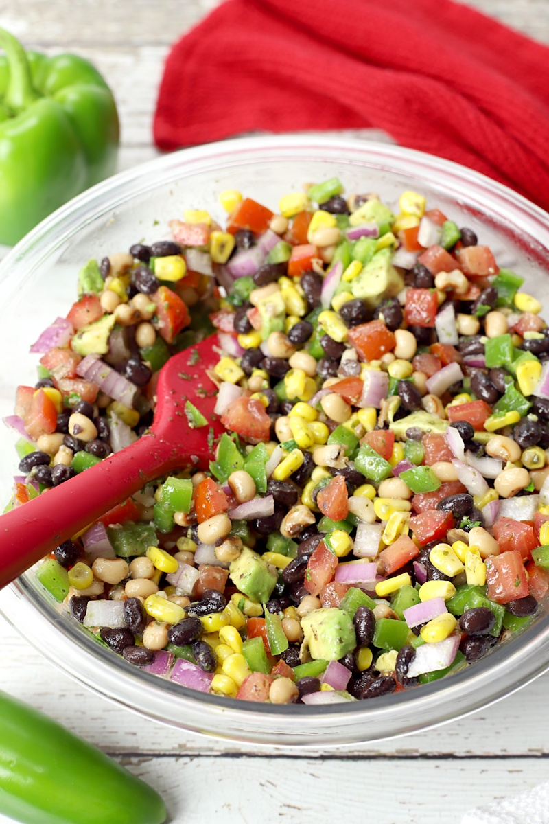 Close up of red spoon stirring salsa in a bowl.
