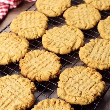 Peanut butter cookies cooling on a rack on the kitchen counter.