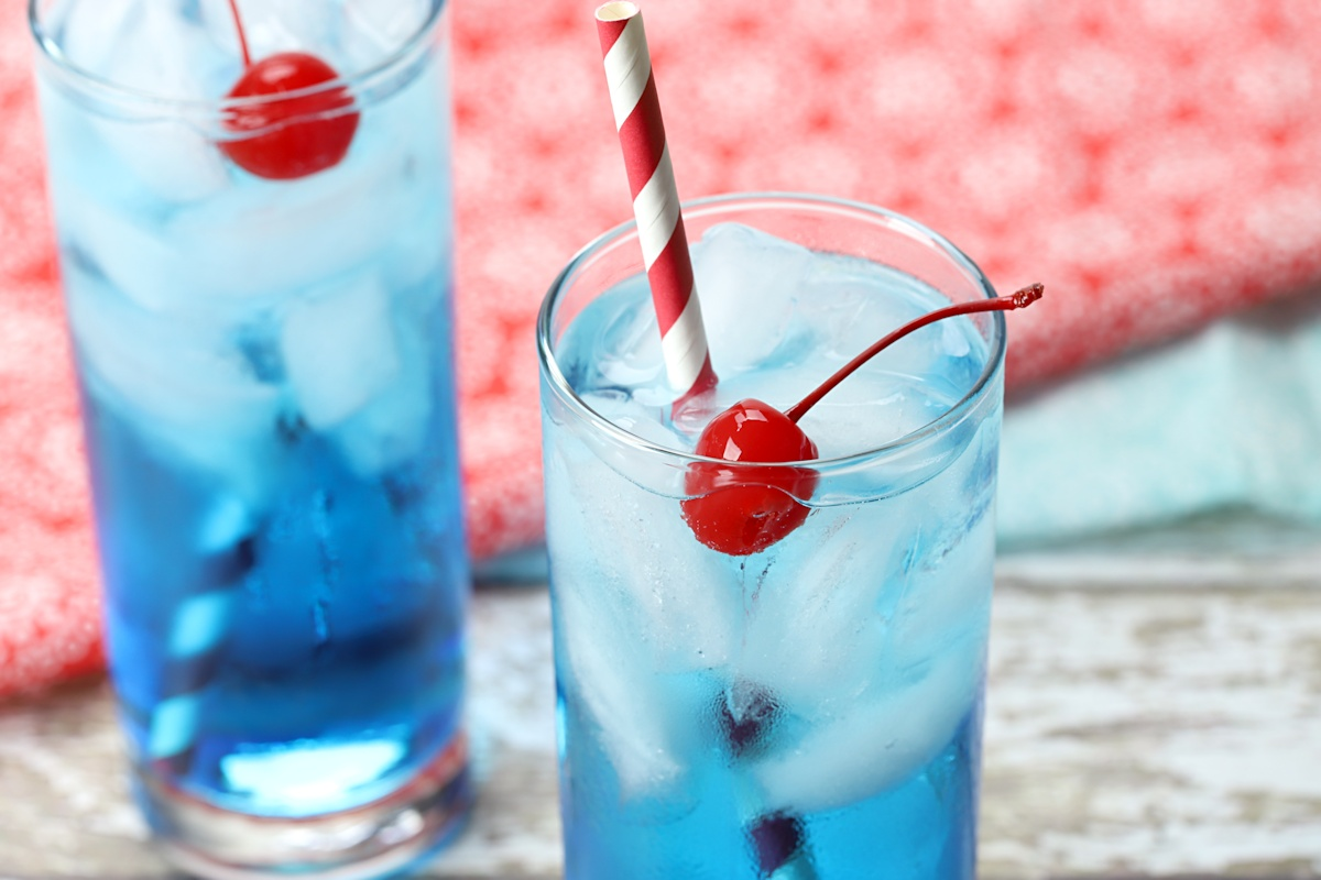 Close up of cherry and straw in a blue drink.