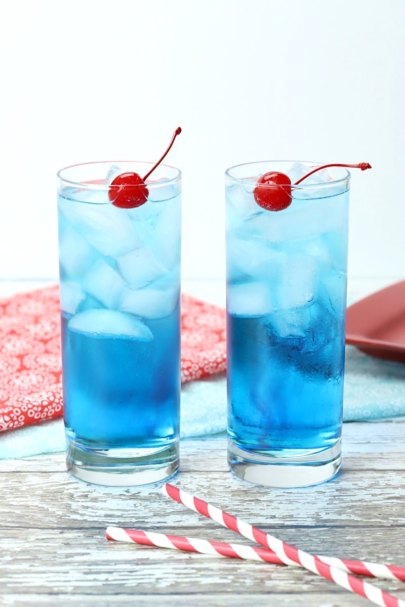 Two blue cocktails on a white wood countertop with cherries and straws.