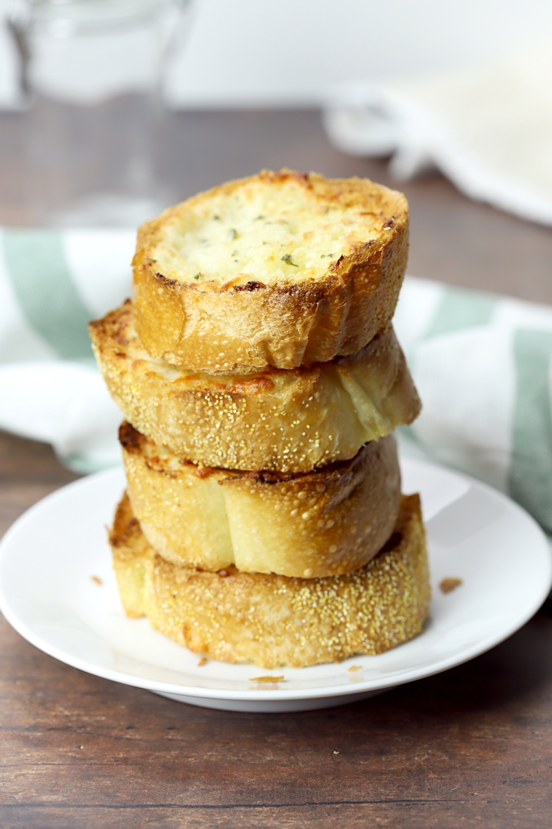 A stack of garlic bread on a white plate.