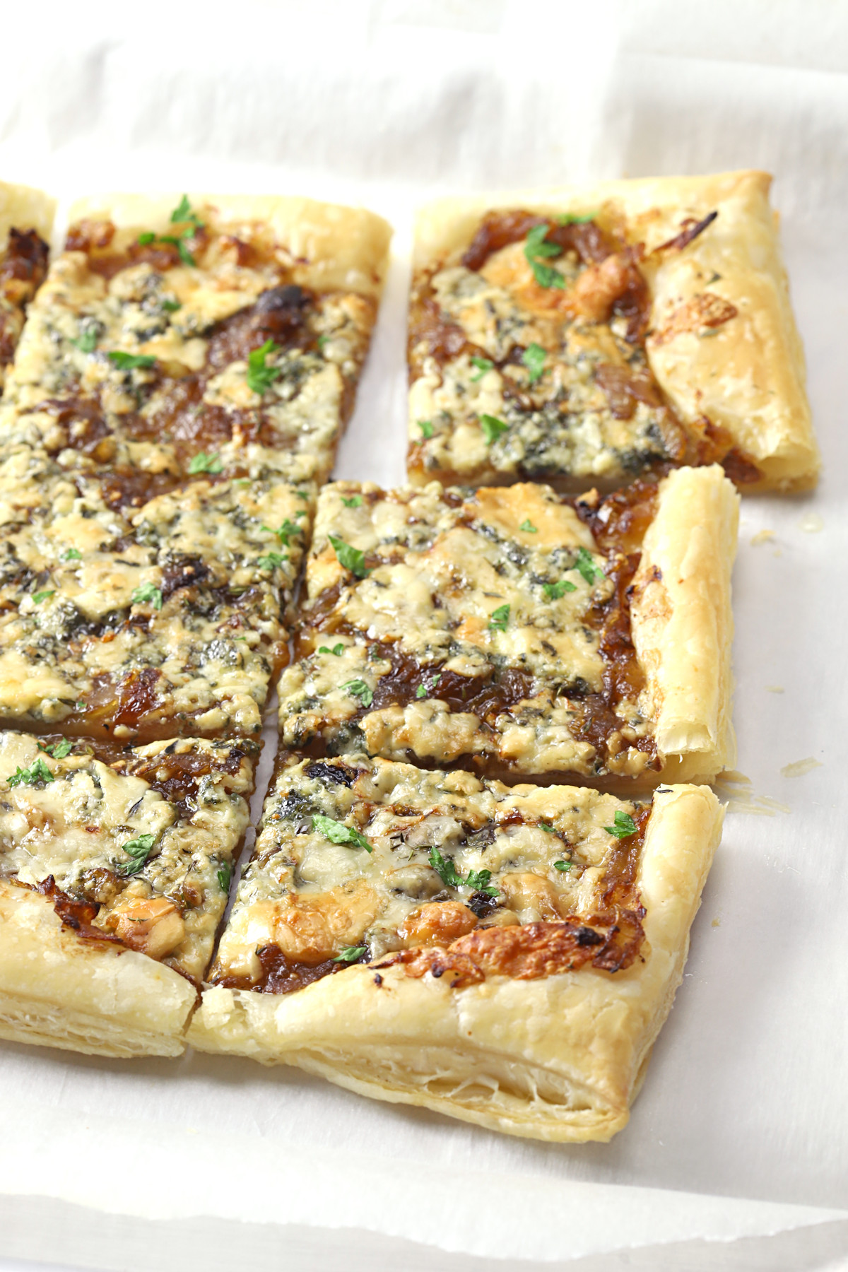 Caramelized onion tart sliced into squares.