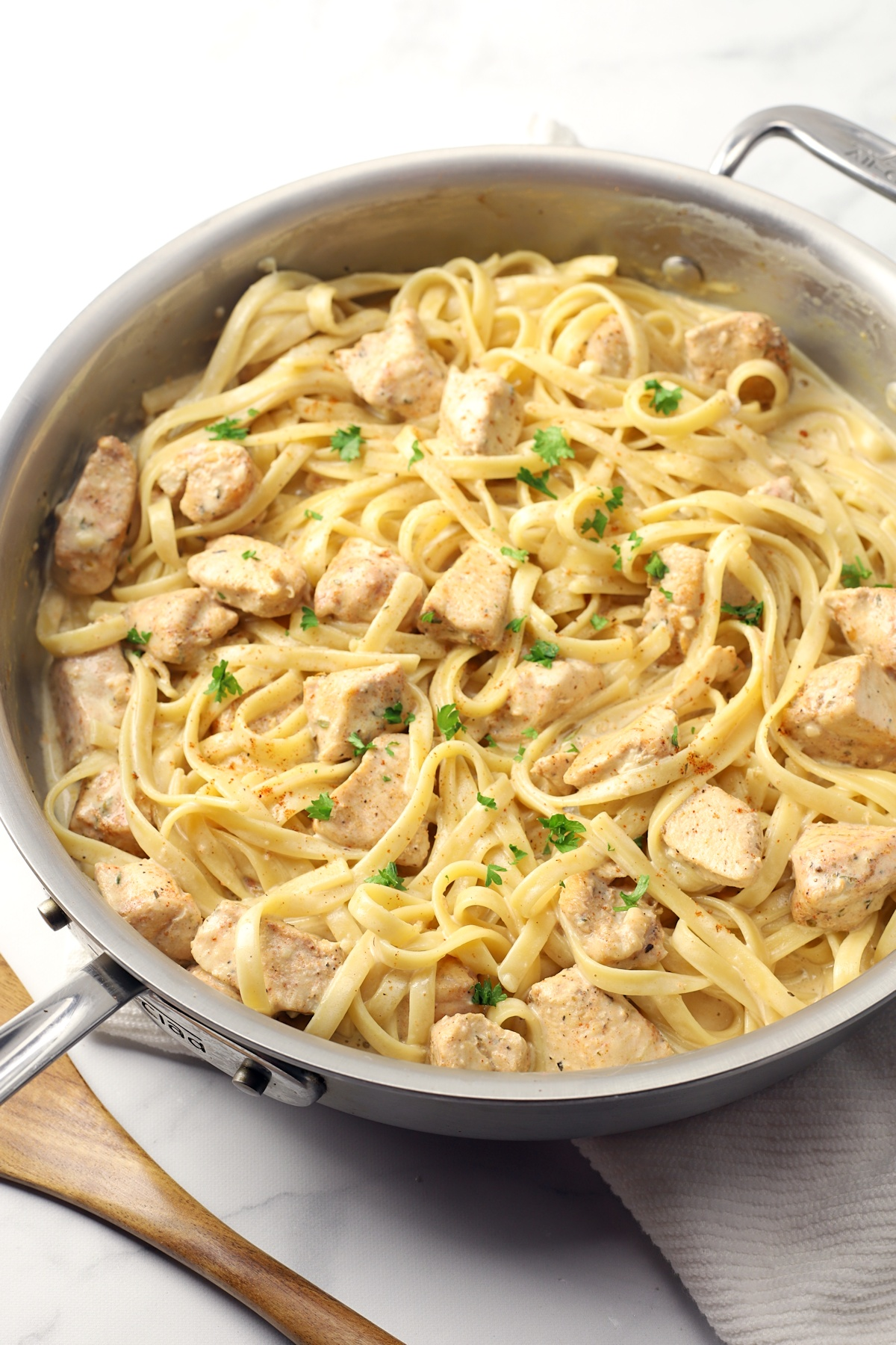 Saute pan filled with pasta and chicken.