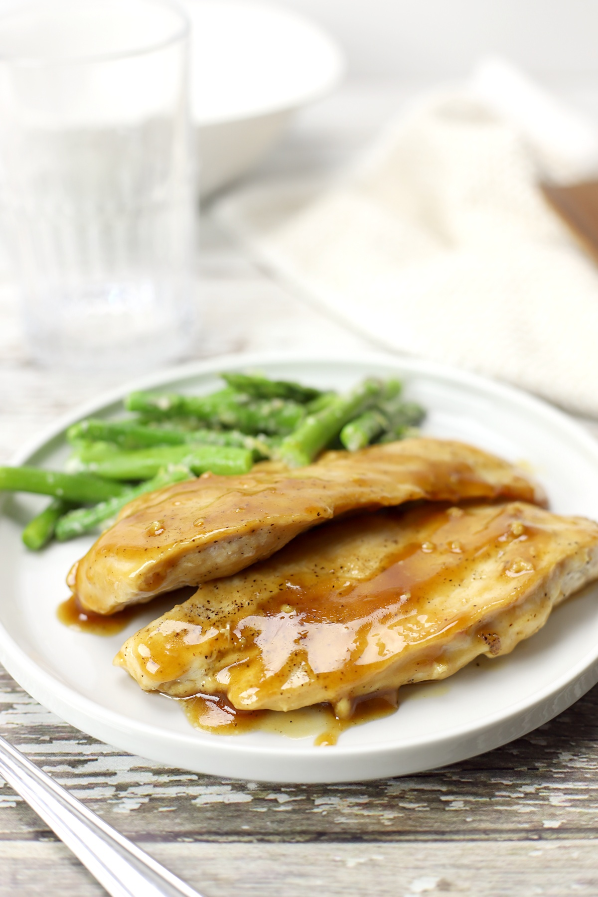 A plate of maple glazed chicken with asparagus.
