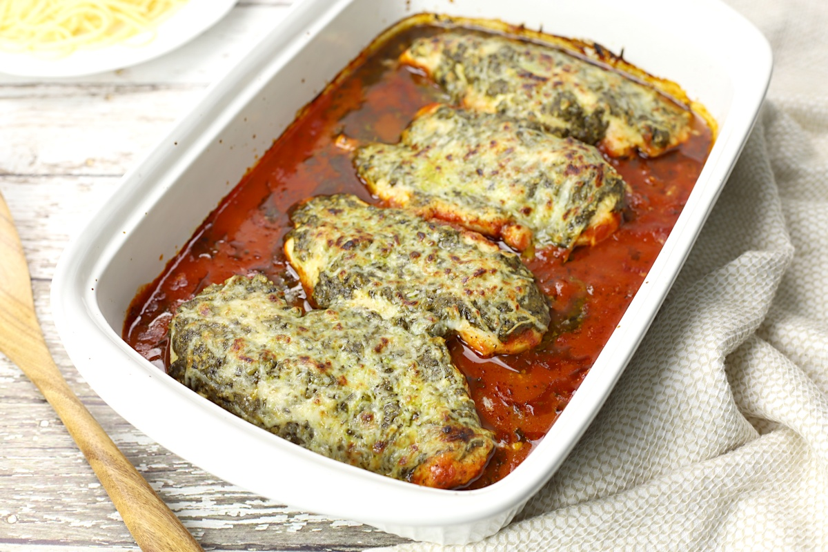 Four pieces of chicken in a lasagna pan.