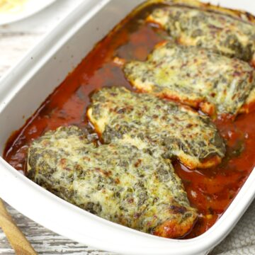 Chicken coated in basil pesto, mozzarella, surrounded by tomato sauce.