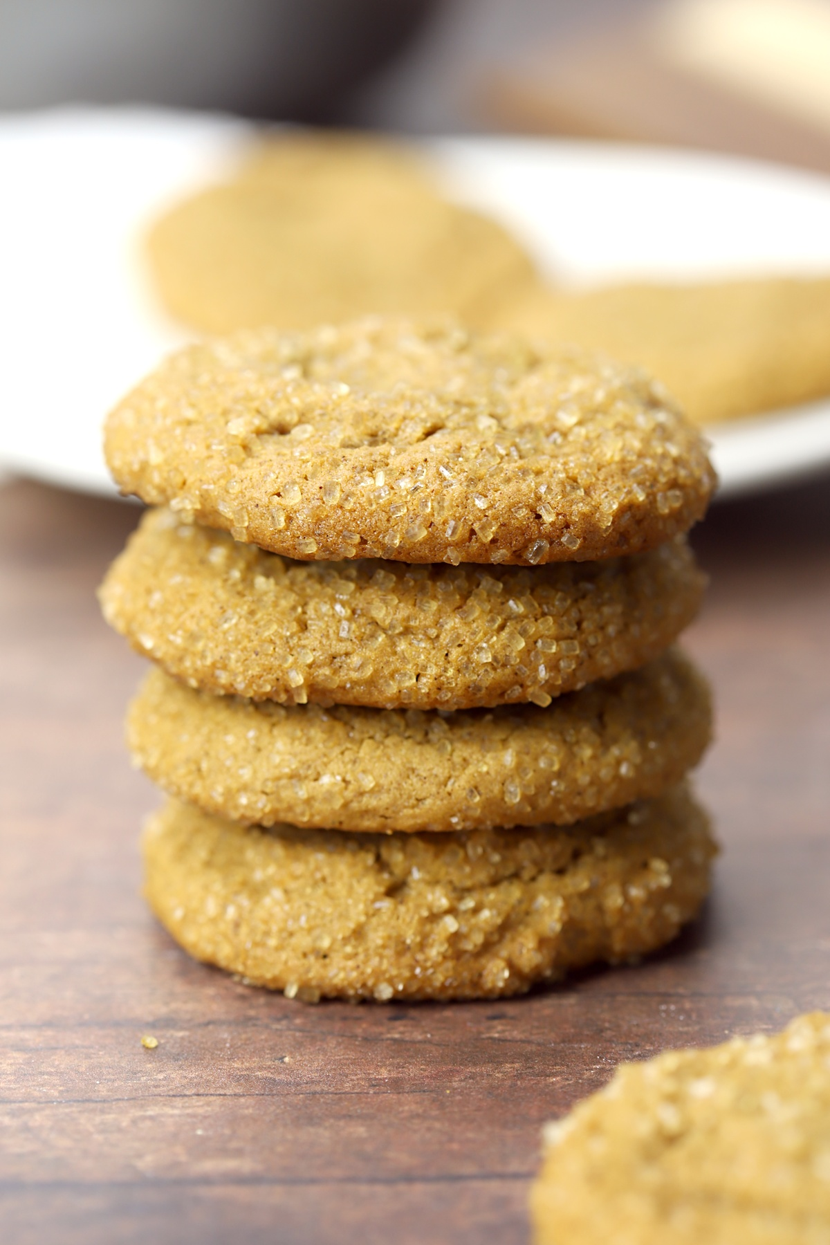Stack of molasses cookies on a wood counter top.
