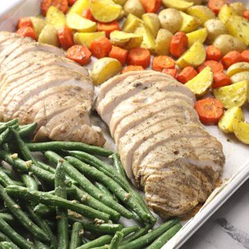 Turkey tenderloin and vegetables on a sheet pan.