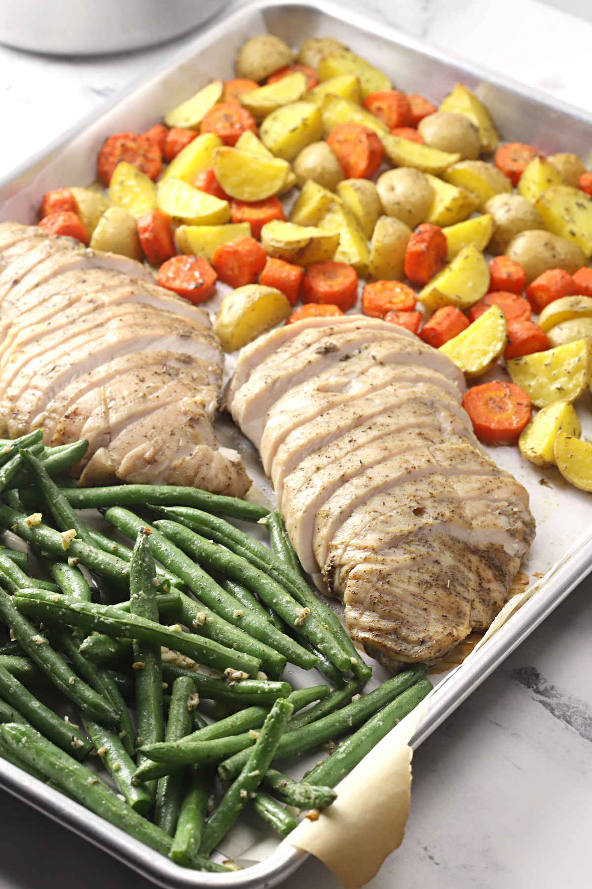 Turkey tenderloin and vegetables on a sheet pan.