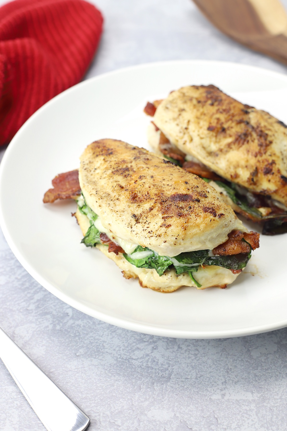 Bacon and spinach stuffed in the middle of chicken breasts, on a white plate.