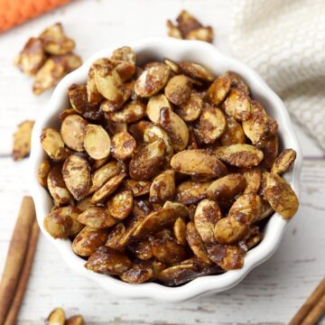 A white bowl of candied pumpkin seeds with cinnamon sticks.