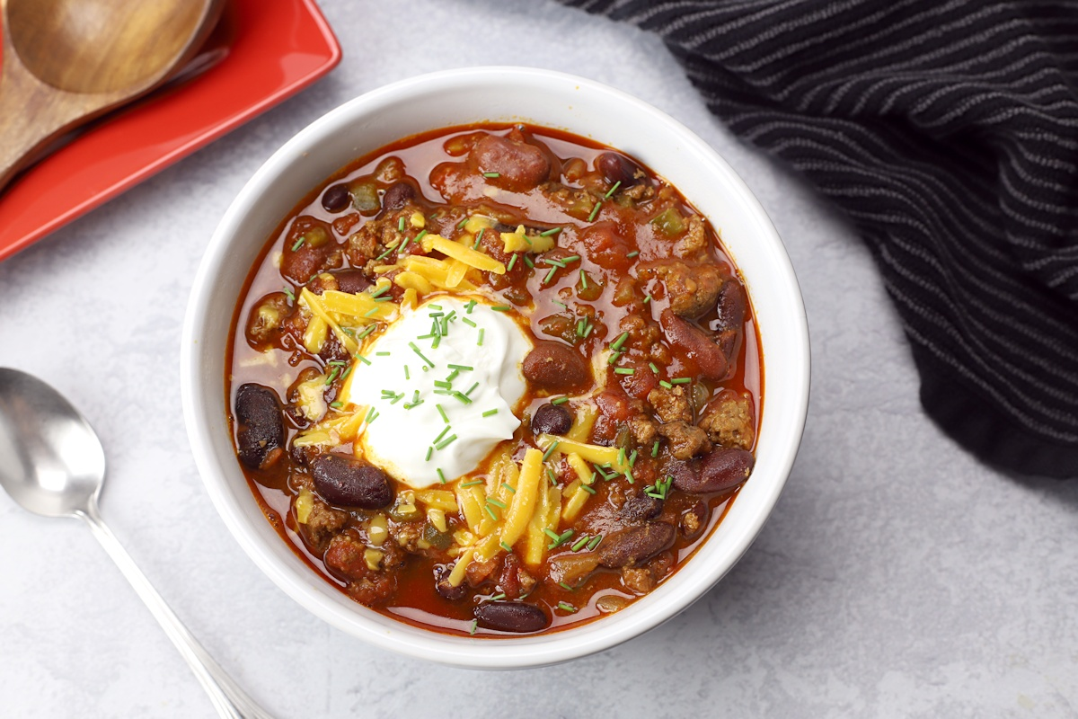 Chili in a white bowl with a spoon.