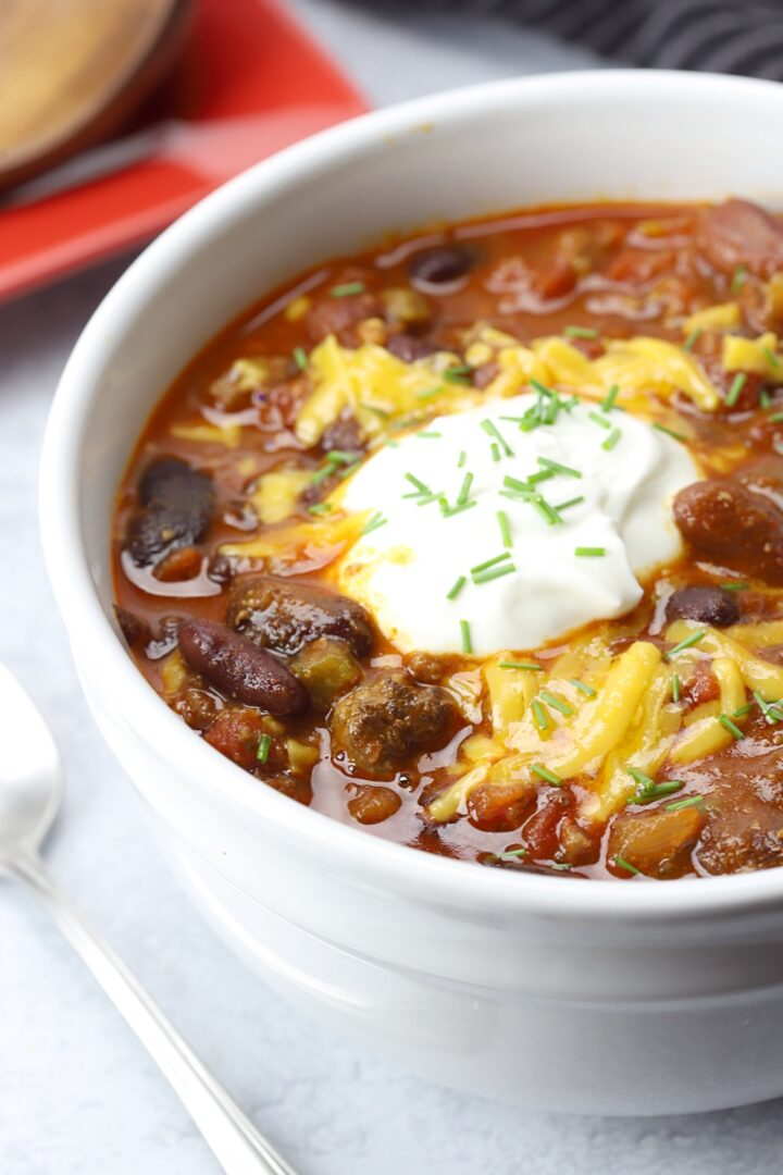 Sour cream and cheese top a bowl of chili.