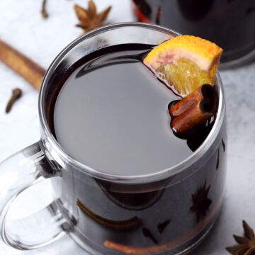 An orange slice and cinnamon stick in a glass of mulled wine.