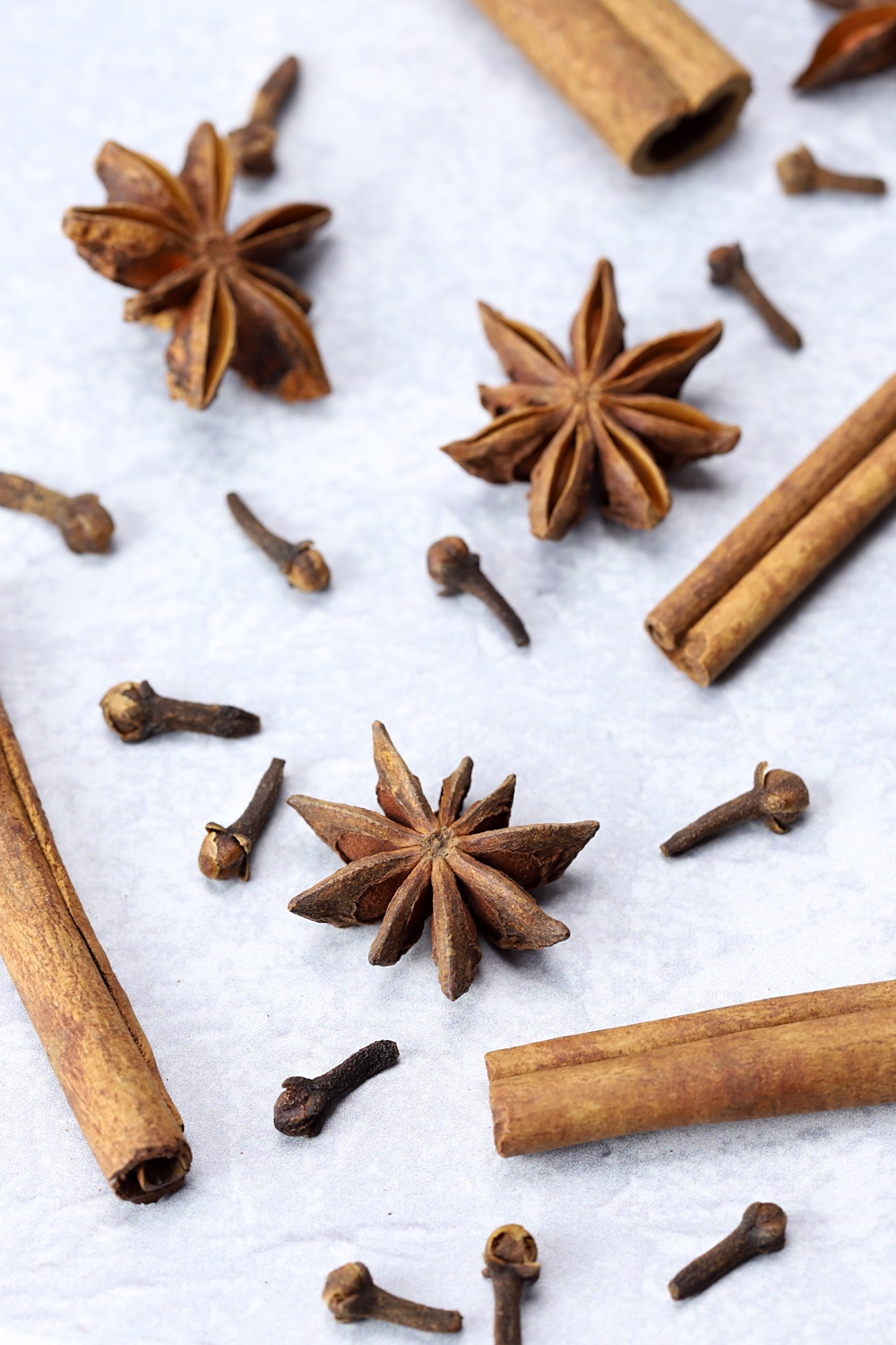 Cinnamon sticks, star anise, and cloves scattered on a surface.