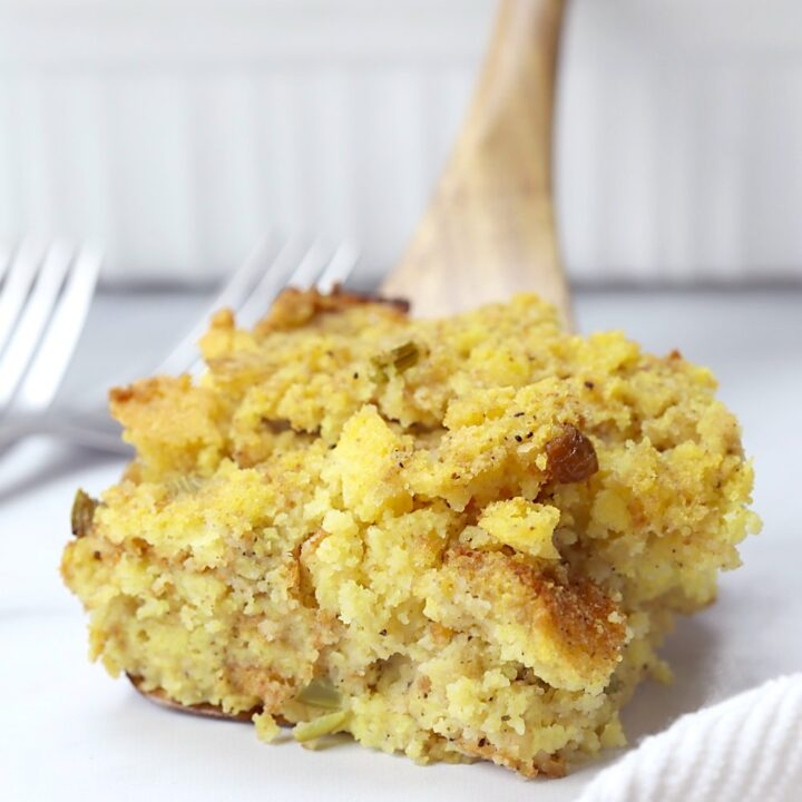 Wooden spatula holding a serving of cornbread dressing.