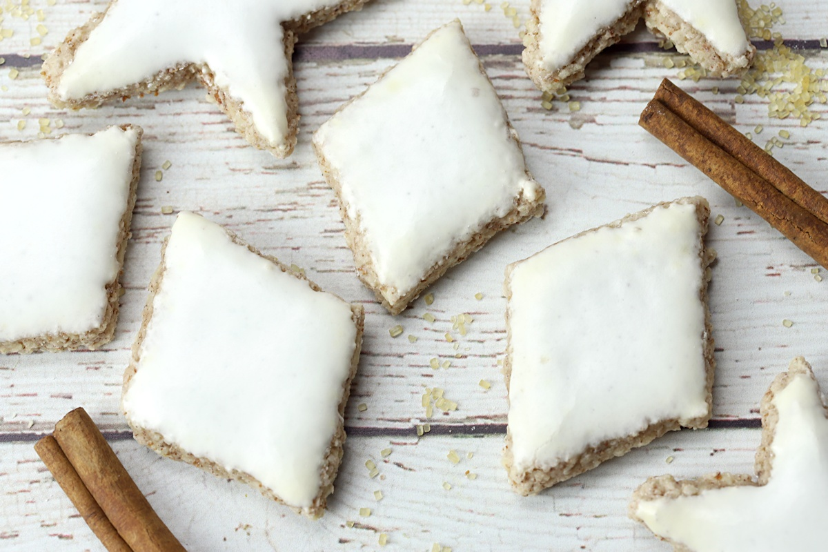 Zimtsterne cookies on a white wood counter top.
