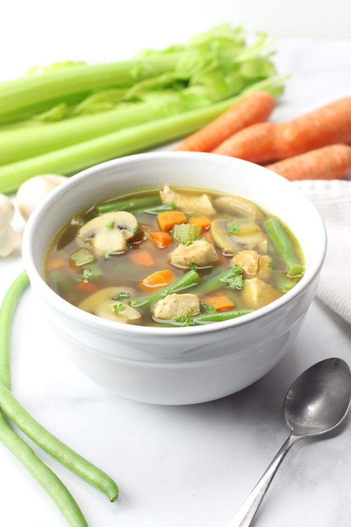 White bowl filled with soup, celery and carrots in the background.