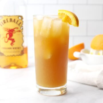 A glass of fireball orange sweet tea on a marble counter top.