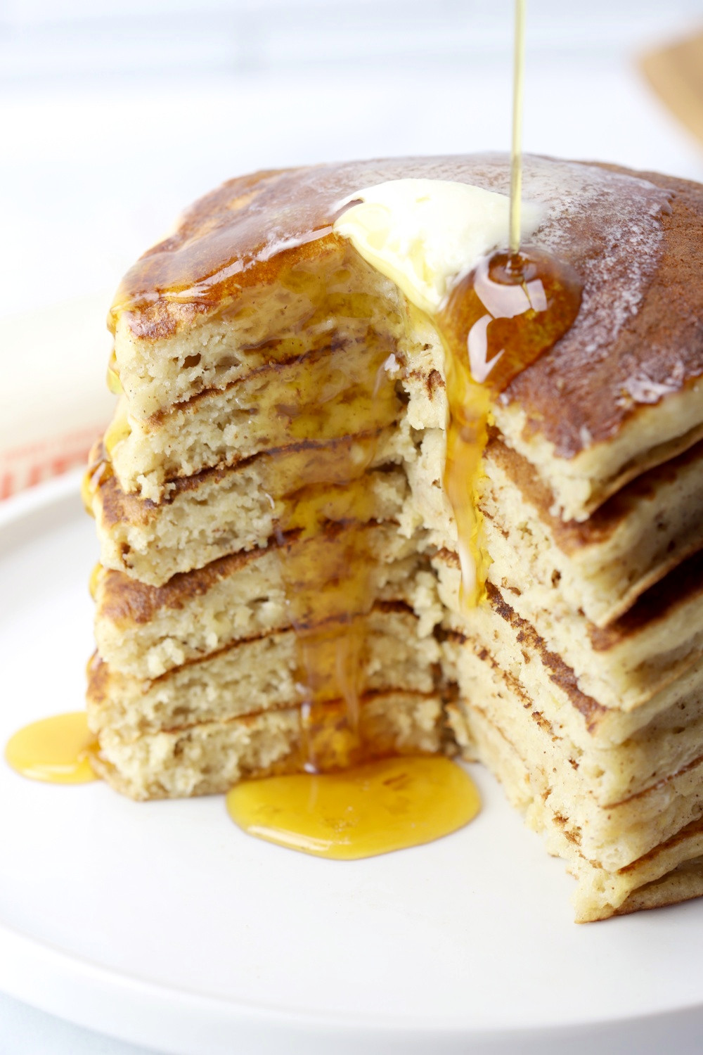 Maple syrup and melting butter dripping down a stack of pancakes.