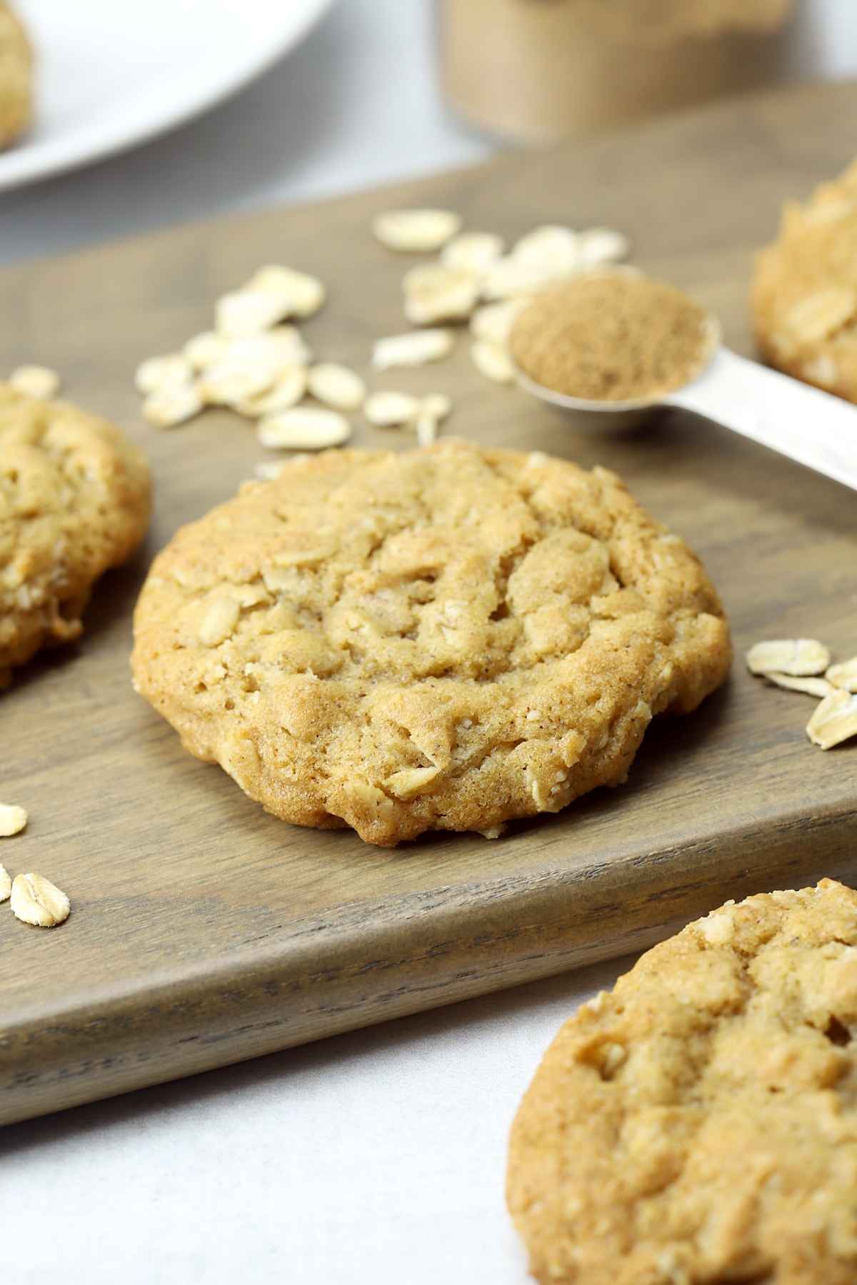 An oatmeal cookie on a wooden cutting board, with oats and chai spice.
