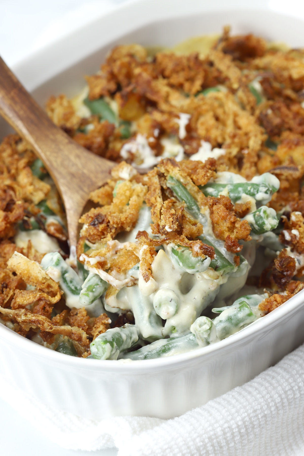 A wooden spoon scoops a serving of green bean casserole.