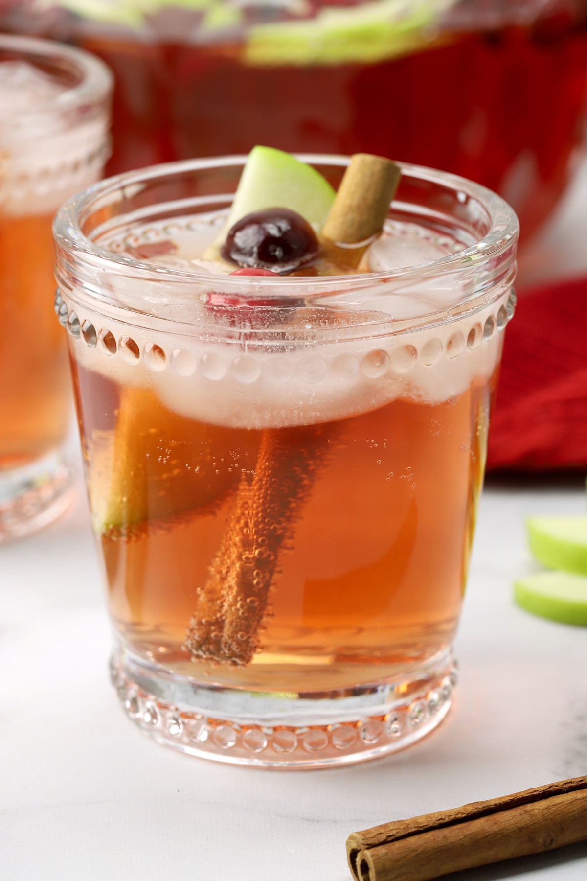 A glass with cinnamon stick, apple wedge, and punch.