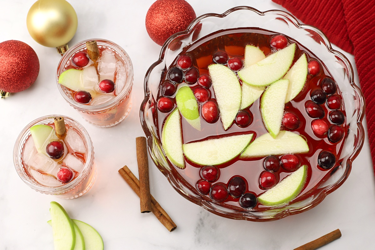 A punch bowl filled with red punch, cranberries, and apple slices.