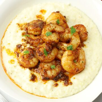 A white bowl filled cajun shrimp and grits.