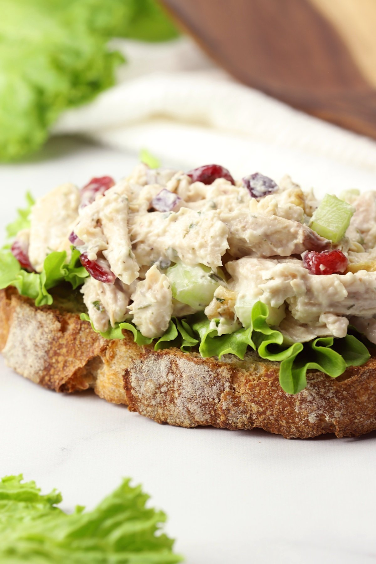 A slice of bread, lettuce, and a scoop of chicken salad.