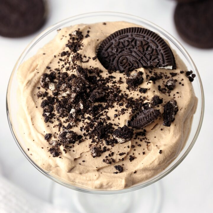 Oreos crumbled on top of a choclate parfait.