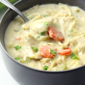 A dark grey bowl filled with chicken soup.