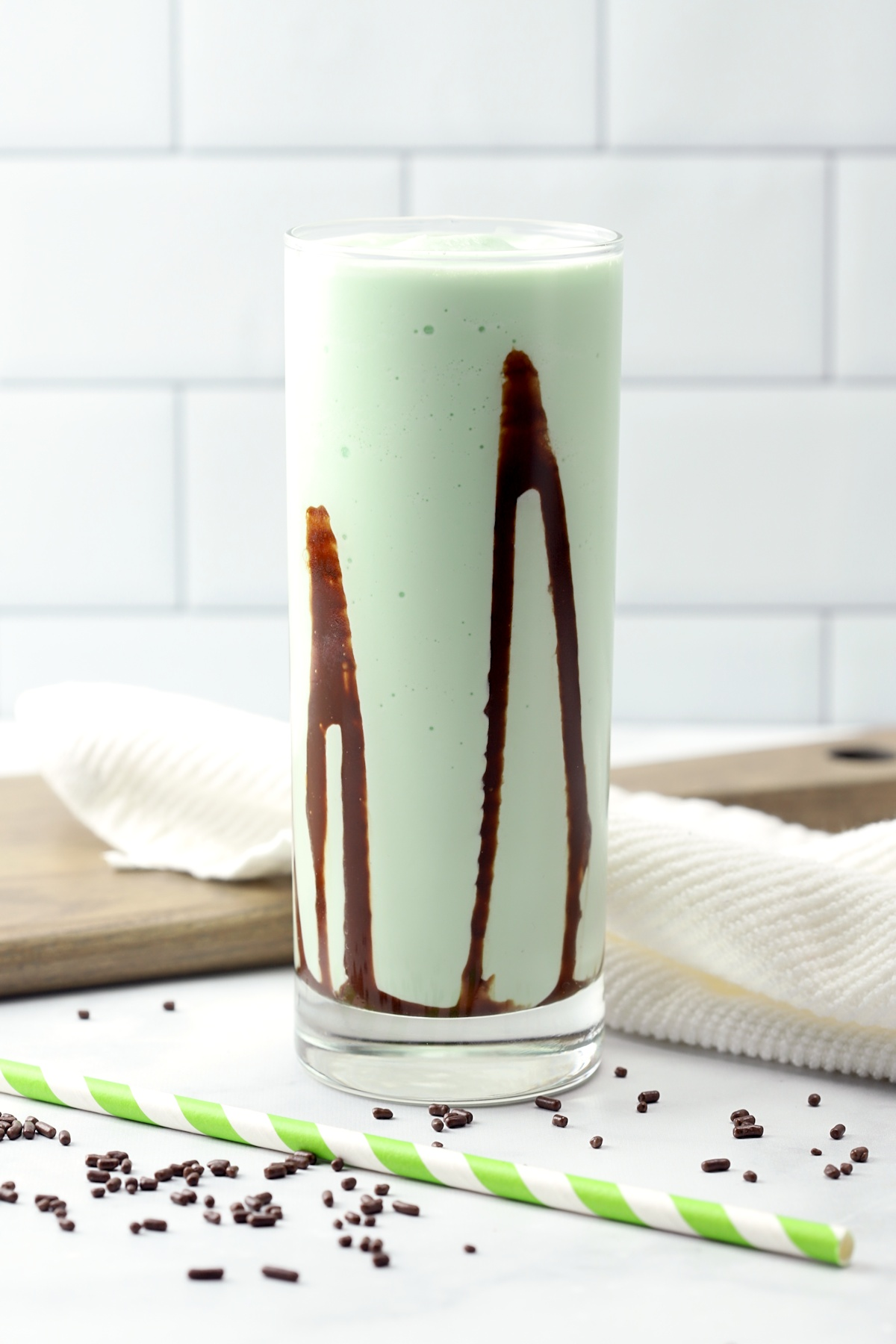 Frozen green alcoholic drink with swirls of chocolate syrup.