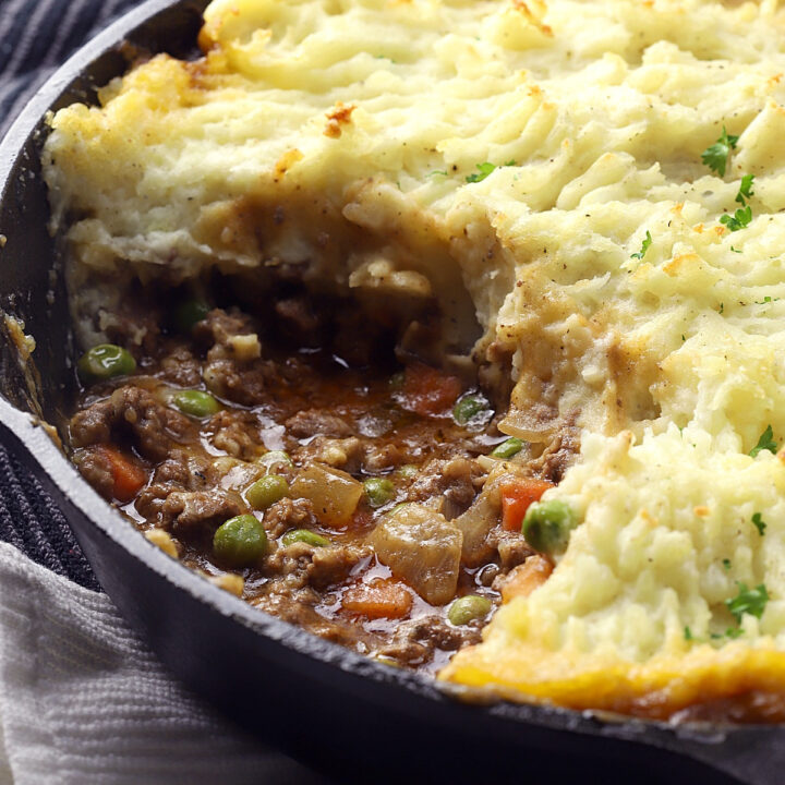 A cast iron pan filled with beef cottage pie and potatoes.